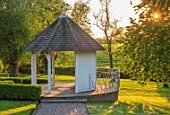 MITTON MANOR, STAFFORDSHIRE: SUMMERHOUSE IN EVENING LIGHT. SUMMER HOUSE, SUMMER HOUSES, SUMMERHOUSES, PATH, BRICK, PATHS, LAWN, ENGLISH, COUNTRY, GARDEN