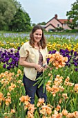 HOWARDS NURSERIES, NORFOLK: CHRISTINE HOWARD WITH IRISES. IRIS BEDS, FIELDS  WITH HOUSE IN BACKGROUND. CORMS, LINES, ROWS, RURAL SCENE, NURSERY