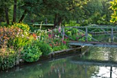 ABLINGTON MANOR GLOUCESTERSHIRE: VIEW ACROSS COLN RIVER TO ISLAND BED AND WOODEN FOOTBRIDGE. REFLECTIONS WATER. CLASSIC COUNTRY GARDEN COTSWOLDS ROMANTIC ROMANCE LAWN