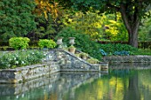 ABLINGTON MANOR GLOUCESTERSHIRE: VIEW ACROSS RIVER COLN TO URNS AND STEPS INTO RIVER. CLASSIC COUNTRY GARDEN JUNE SUMMER ROMANCE ROMANTIC