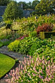 ABLINGTON MANOR, GLOUCESTERSHIRE: LAWN, STONE PATH, BORDER WITH PERSICARIA BISTORTA SUPERBA, HOSTAS, ROSES, BORDERS, SUMMER
