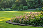 ABLINGTON MANOR, GLOUCESTERSHIRE: LAWN, STONE PATH, BORDER WITH PERSICARIA BISTORTA SUPERBA, HOSTAS, BORDERS, SUMMER