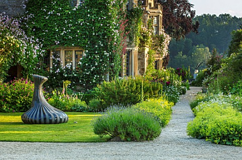 ASTHALL_MANOR_OXFORDSHIRE_SCULPTURE_THE_SINGER_OF_TALES_BY_JOHN_ISHERWOOD_LAWN_PATH_WITH_ALCHEMILLA_
