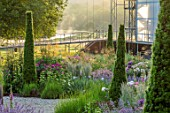 WORMSLEY, BUCKINGHAMSHIRE: THE OPERA GARDEN, DESIGNER HANNAH GARDNER: THE GARDEN IN MORNING LIGHT. SUNRISE, SUMMER, YEW