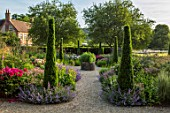 WORMSLEY, BUCKINGHAMSHIRE: THE OPERA GARDEN, DESIGNER HANNAH GARDNER: PATH, YEWS, BORDERS, STIPA GIGANTEA. HOME FARM, PAEONIA VICTOIRE DE LA MARNE. ENGLISH, COUNTRY, GARDEN, SUMMER