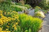SOUTH HAYES, OXFORD: DESIGNER SARAH NAYBOUR: GARDEN ON A SLOPE - GRAVEL PATHS, ACHILLEA MOONSHINE, STIPA TENUISSIMA. SLOPING, SLOPES, WOODEN BENCHES, SEATS, OAK SLEEPERS