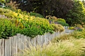 SOUTH HAYES, OXFORD: DESIGNER SARAH NAYBOUR: GARDEN ON A SLOPE - STIPA TENUISSIMA. SLOPING, SLOPES, OAK SLEEPERS, PHLOMIS RUSSELIANA