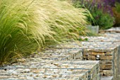 SOUTH HAYES, OXFORD: DESIGNER SARAH NAYBOUR: GARDEN ON A SLOPE - STIPA TENUISSIMA ABOVE GABIONS. STONE, METAL, SEAT, SEATING, PERENNIALS, SUMMER, GRASSES