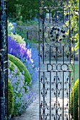 TOWN PLACE GARDEN, SUSSEX: VIEW THROUGH HALF OPENED WROUGHT IRON GATE TO PATH, HERBACEOUS BORDER. SUMMER, ENGLISH, GARDEN, COUNTRY