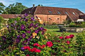 THE WALLED GARDEN AT COWDRAY, WEST SUSSEX: CLEMATIS AND RED ROSE WITH FOUNTAIN AND LAWN.