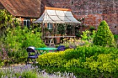 THE WALLED GARDEN AT COWDRAY, WEST SUSSEX: OUTDOOR DINING, SEATING AREA WITH RUSTY METAL PERGOLA, AWNING, PLACE TO SIT, DINING, AL FRESCO, ENTERTAINING
