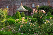 THE WALLED GARDEN AT COWDRAY, WEST SUSSEX: BORDERS, ROSES, OUTDOOR DINING, SEATING AREA TABLE, CHAIRS, BOX PARTERRES, GREEN, ENGLISH, COUNTRY, GARDEN, AWNING, GAZEBO, AL FRESCO