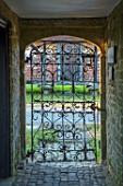 THE WALLED GARDEN AT COWDRAY, WEST SUSSEX: VIEW OUT OF ORNATE METAL ENTRANCE GATE TO GARDENS. ENGLISH, COUNTRY, GARDEN