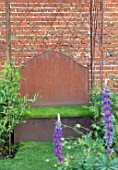 THE WALLED GARDEN AT COWDRAY, WEST SUSSEX: RUSTY METAL SEAT, BENCH, TURF, WALL, PLACE TO SIT, LUPINS, ENGLISH, COUNTRY, GARDENS