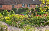 THE WALLED GARDEN AT COWDRAY, WEST SUSSEX: ENGLISH, COUNTRY, GARDEN, BORDERS OF RED, FLOWERED ROSES, SUMMER, BOX EDGED, BEDS, BUXUS, CLEMATIS, PATHS
