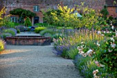 THE WALLED GARDEN AT COWDRAY, WEST SUSSEX: PATH, BORDERS WITH LAVENDER, VERBENA BONARIENSIS, BRICK RAISED POND, POOL, WATER FEATURE, ENGLISH, COUNTRY, GARDENS, SUMMER