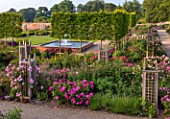 WYNYARD HALL, COUNTY DURHAM: WALLED ROSE GARDEN. ROSES, FLOWERS, SUMMER, JUNE BEDS. WOODEN, TRELLIS, SUPPORTS, CLIMBERS, WALLS, FOUNTAIN, WATER FEATURE, POOL, PLEACHED TREES