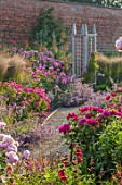 WYNYARD HALL, COUNTY DURHAM: GRAVEL PATH, ROSES , WOODEN TRELLIS SUPPORTS, WALL, WALLED ROSE GARDEN, SUMMER, JUNE