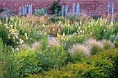 WYNYARD HALL, COUNTY DURHAM: WALLED ROSE GARDEN. BORDERS, SUMMER, JUNE, YELLOW, KNIPHOFIA, STIPA TENUISSIMA, ROSES, WOODEN, TRELLIS, SUPPORTS