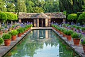 HAMPTON COURT CASTLE, HEREFORDSHIRE:THE DUTCH GARDEN, JULY - BLUE AGAPANTHUS IN TERRACOTTA CONTAINERS , RECTANGULAR FORMAL POOL, CANAL, BUILDING, GARDEN, ENGLISH, WATER