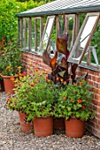 MORTON HALL GARDENS, WORCESTERSHIRE: KITCHEN GARDEN, JULY, TERRACOTTA CONTAINERS PLANTED WITH CANNAS AND DAHLIA NEW BABY
