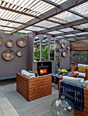 TANYA SOUTHWORTH GARDEN, LONDON, DESIGNER ANOUSHKA FEILER: OUTDOOR LIVING ROOM. SOFAS, FIRE, MIRRORS, RENDERED WALL, SMALL, FORMAL, TOWN, URBAN