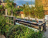 TANYA SOUTHWORTH GARDEN, LONDON, DESIGNER ANOUSHKA FEILER: TABLE, BENCHES, CANDLES, BAMBOOS IN CONTAINERS, MIRRORS, SMALL, FORMAL, TOWN, URBAN
