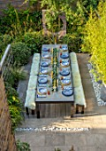 TANYA SOUTHWORTH GARDEN, LONDON, DESIGNER ANOUSHKA FEILER: VIEW ONTO TABLE, BENCHES, CANDLES, BAMBOOS IN CONTAINERS, MIRRORS, SMALL, FORMAL, TOWN, URBAN, ENTERTAINING