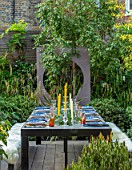 TANYA SOUTHWORTH GARDEN, LONDON, DESIGNER ANOUSHKA FEILER: TABLE, BENCHES, CANDLES, DOG, PET, RENDERED WALL WITH CIRCULAR OPENING, SMALL, FORMAL, TOWN, URBAN