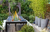 TANYA SOUTHWORTH GARDEN, LONDON, DESIGNER ANOUSHKA FEILER: TABLE, BENCHES, CANDLES, RENDERED WALL WITH CIRCULAR OPENING, CONTAINERS WITH BAMBOO, SMALL, FORMAL, TOWN, URBAN