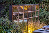 TANYA SOUTHWORTH GARDEN, LONDON, DESIGNER ANOUSHKA FEILER: ANTIQUE MIRROR, TABLE, BENCHES, SMALL, FORMAL, TOWN, URBAN, REFLECTED, REFLECTIONS, NIGHT, LIGHTS, LIGHTING