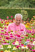 MEADOW FARM GARDEN AND NURSERY, WORCESTERSHIRE: ROB COLE AMONGST ECHINACEAS IN THE NURSERY. PERENNIALS, FLOWERS, FLOWERING, LATE, SUMMER, PINK