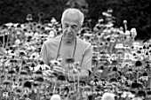 MEADOW FARM GARDEN AND NURSERY, WORCESTERSHIRE: BLACK AND WHITE IMAGE OF ROB COLE AMONGST ECHINACEAS IN THE NURSERY. PERENNIALS, FLOWERS, FLOWERING, LATE, SUMMER