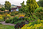 MEADOW FARM GARDEN AND NURSERY, WORCESTERSHIRE: EVENING LIGHT ON LAWN AND BORDERS. ENGLISH, COUNTRY, GARDEN, BORROWED LANDSCAPE
