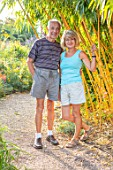 MEADOW FARM GARDEN AND NURSERY, WORCESTERSHIRE: GARDEN OWNERS ROB AND DIANE COLE BESIDE PHYLLOSTACHYS VIVAX AUREOCAULIS