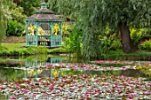 BENNETTS WATER GARDENS, DORSET: LAKE, WATER LILIES, WATERLILIES, BLUE, PAINTED, GAZEBO, SUMMERHOUSE, SUMMER, ENGLISH, COUNTRY, GARDEN, POND, POOL, PINK, FLOWERING, WILLOWS