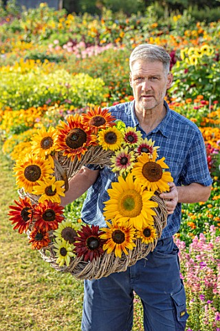 ASTON_POTTERY_OXFORDSHIRE_STEPHEN_BAUGHAN_HOLDS_SUNFLOWER_WREATH__HELIANTHUS_VELVET_QUEEN_SUMMER_BRE