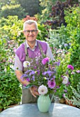CLAUS DALBY GARDEN, DENMARK: CLAUS DALBY ARRANGING A BOUQUET OF FLOWERS FROM THE GARDEN