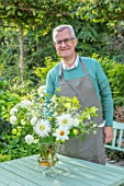 CLAUS DALBY GARDEN, DENMARK: CLAUS DALBY ARRANGING A BOUQUET OF WHITE FLOWERS FROM THE GARDEN