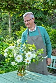 CLAUS DALBY GARDEN, DENMARK: CLAUS DALBY IN HIS GARDEN ARRANGING A BOUQUET OF WHITE FLOWERS IN HIS GARDEN