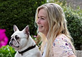 PYTTS HOUSE, OXFORDSHIRE: OWNER ANNA DE KEYSER WITH HER DOG MABLE ON THE TERRACE OUTSIDE THE HOUSE, PATIO, SUMMER. PARASOL