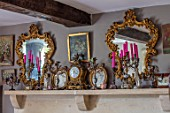 PYTTS HOUSE, OXFORDSHIRE: THE DINING ROOM. MIRRORS, PICTURES, CANDELABRAS AND CLOCKS ON MANTELPIECE ABOVE THE FIREPLACE