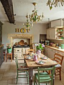 PYTTS HOUSE, OXFORDSHIRE: KITCHEN WITH GREEN CHAIRS, WOODEN TABLE, AGA