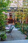 HORSE SHOE BEND, LONDON. DESIGNER MARTHA KREMPEL: COURTYARD GARDEN: BETULA NIGRA HERITAGE, FORMAL, SMALL, GARDENS, LIGHTING, EVENING LIGHT, CHAIRS, LOUNGERS, PATIO