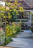 HORSE SHOE BEND, LONDON. DESIGNER MARTHA KREMPEL: VIEW OUT OF KITCHEN TO COURTYARD GARDEN, PATIO, BETULA NIGRA HERITAGE, RUDBECKIA DEAMII, ROSE - ROSA LADY EMMA HAMILTON
