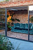 HORSE SHOE BEND, LONDON. DESIGNER MARTHA KREMPEL: INDOOR CORRIDOR WITH HOUSEPLANTS: STRELITZIA, HOWEA FOSTERIANA, ALOES, PILEA, INDOOR FERN, SETTEE, GLASS DOORS
