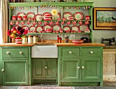 ALHAM FARM, SOMERSET: CORNISHWARE: KITCHEN, DRESSER PAINTED GREEN, PAINT IS SAGE GREEN, RED STRIPE CORNISHWARE, OLD BOTTLES