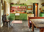 ALHAM FARM, SOMERSET: CORNISHWARE: KITCHEN, DRESSER PAINTED GREEN, PAINT IS SAGE GREEN, RED STRIPE CORNISHWARE, OLD BOTTLES, STONE FLOORING, WOODEN TABLE