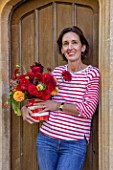 ALHAM FARM, SOMERSET: CORNISHWARE: KARINA RICKARDS HOLDING FLOWERS AT HER FRONT DOOR