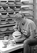 ALHAM FARM, SOMERSET: CORNISHWARE: THE POTTERY - VICKY APPLYING ICONIC BLUE STRIPE BY HAND TO FIRED BOWLS, BLACK AND WHITE